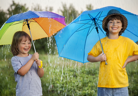 two persons only: two happy brother with umbrella summer outdoors