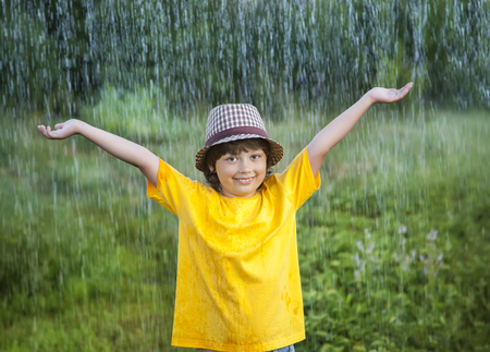 two persons only: happy boy in rain summer outdoors
