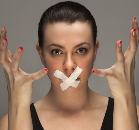 gagged: beauty girl with tape on lips Stock Photo