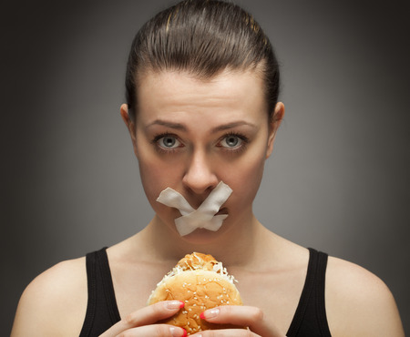 vegetarian hamburger: Diet concept: woman holding burger with mouth sealed
