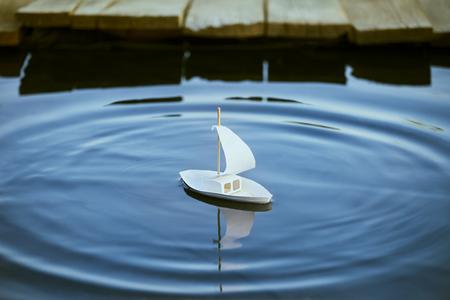 Blanc jouet bateau à un quai dans un étang en été