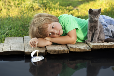 boy and his beloved kitten playing with a boat from pier in a pond summer evening Stock Photo