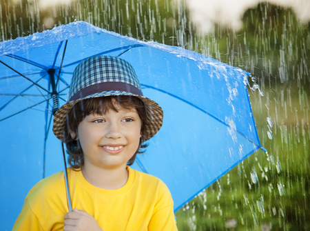 two persons only: happy boy with umbrella outdoors, child with an umbrella walks in the rain
