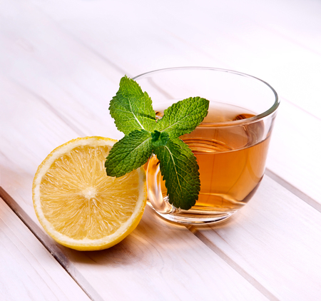beauty and health: cup of tea, glass teapot, mint and lemon on a wooden table