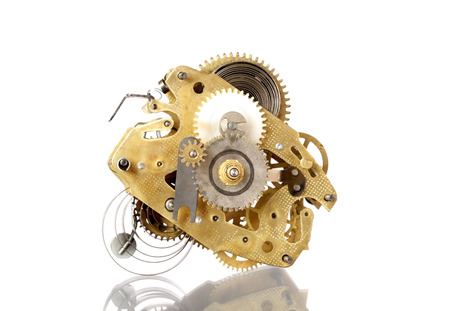 clockworks mechanism of old vintage watch on a white background with reflection