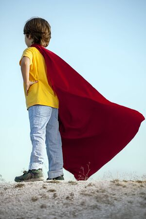 child boy: Boy playing superheroes on the sky background, child superhero in a red cloak on a hill