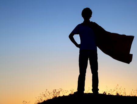 film title: Boy playing superheroes on the sky background, silhouette of teen superhero in a raincoat on the hill