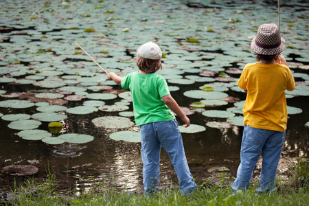 Happy boys go fishing on the river, Two children of the fisherman with a fishing rod on the shore of the lake photo