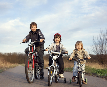 three brothers ride bikes outdoors photo