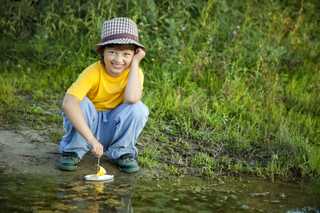 boy play with toy ship in water, chidlren in park play with boat in river Reklamní fotografie
