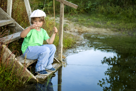 sitting people: Happy boy go fishing on the river, one children fisherman with a fishing rod on the shore of the lake