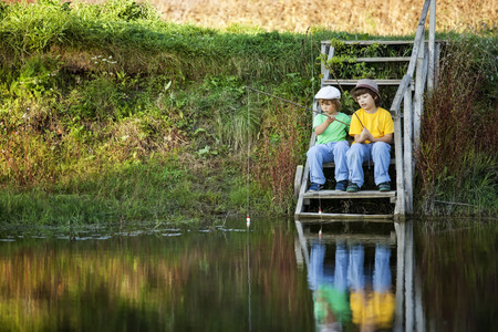 two children: Happy boys go fishing on the river, Two children of the fisherman with a fishing rod on the shore of the lake