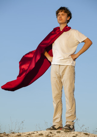 business shirts: Boy playing superheroes on the sky background, teenage superhero in a red cloak on a hill Stock Photo
