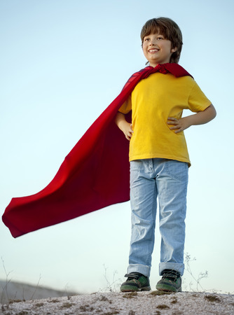 film title: Boy playing superheroes on the sky background, child superhero in a red cloak on a hill