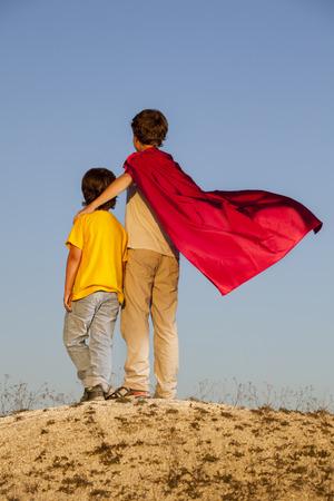 niños vistiendose: Dos niños jugando superhéroes en el fondo del cielo, Superhéroe protege joven amigo