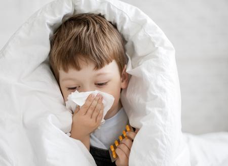 jongen veegt zijn neus met een papieren zakdoekje
