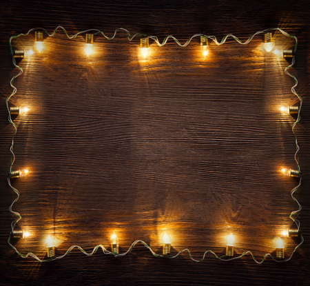 celebration garland of light bulbs on wooden background copy space for inscriptions