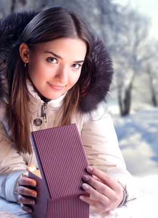 Girl in winter jacket opens a Christmas present on background of a winter forest in the new year