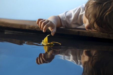 boy play with autumn leaf ship in water, chidren in park play with boat in river photo