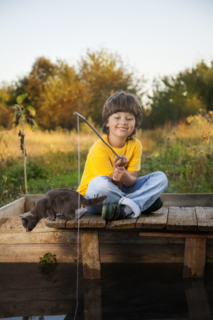 children pond: Happy boy go fishing on the river with pet, child and kitten of the fisherman with a fishing rod on the shore of the lake Stock Photo