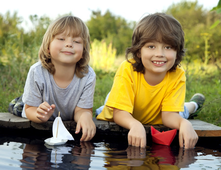 baby toys: Two boys allowed paper boats from the pier of the river