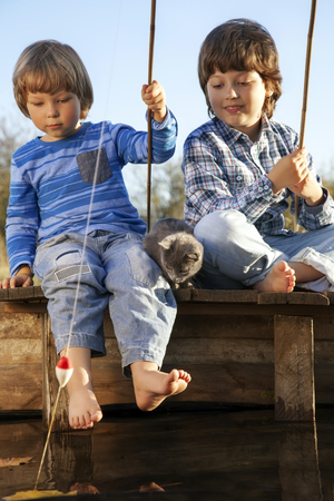 two children: Happy boys go fishing on the river with pet, Two children and kitten of the fisherman with a fishing rod on the shore of the lake Stock Photo