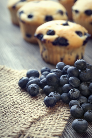 sweet pastries: muffin with blueberries on a wooden table. fresh berries and sweet pastries on the board