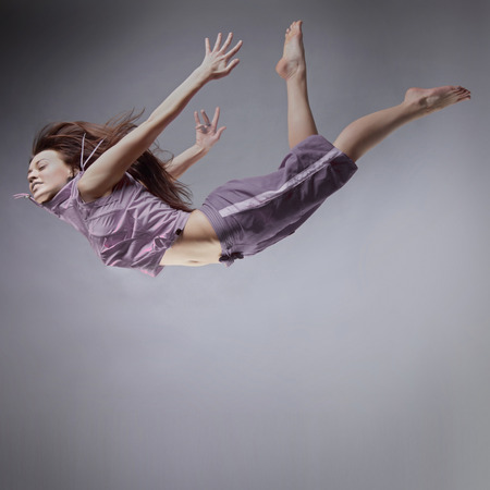 flying man: girl flying, jump and coast, on a gray background