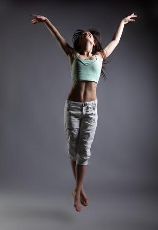 persona saltando: muchacha de la belleza de la danza en el fondo gris. persona saltando, volando en el aire Foto de archivo