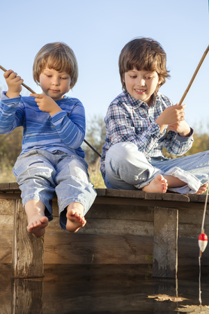 two children: Happy boys go fishing on the river , Two children of the fisherman with a fishing rod on the shore of the lake Stock Photo