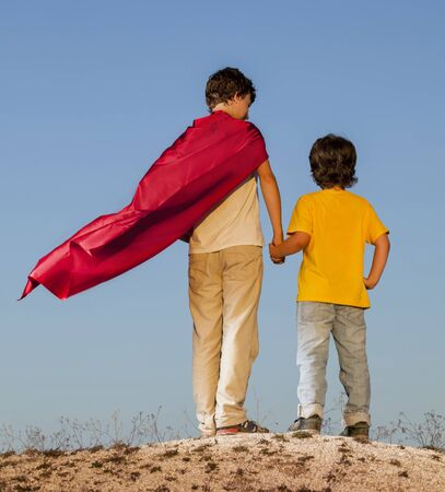 Two boys playing superheroes on the sky background