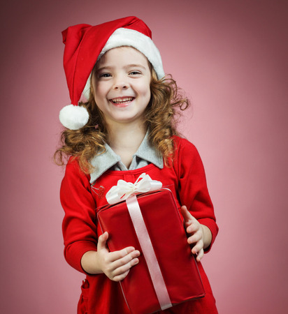 Happy little girl open red gift box photo