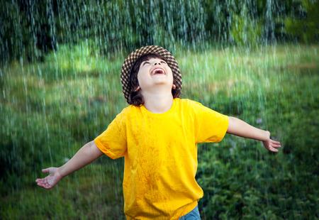 mojada: niño feliz en la lluvia de verano al aire libre