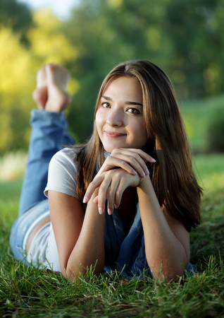 beautiful teenager girl lying in a sunny spring park smiling summer nature photo