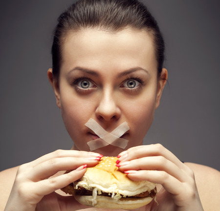 Diet concept: woman holding burger with mouth sealed photo