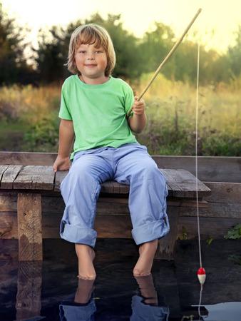 pecheur: Happy boy aller à la pêche sur la rivière, l'un des enfants pêcheur avec une canne à pêche sur la rive du lac