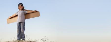 空を飛ぶ空の夢に対する翼の段ボール箱で幸せな少年