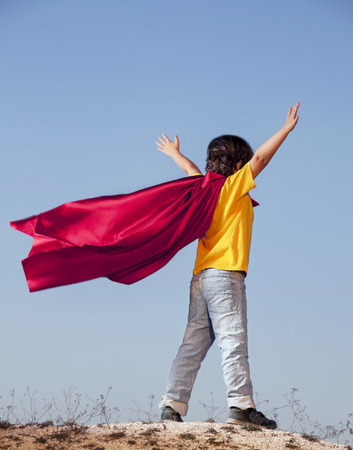film title: Boy playing superheroes on the sky background, teenage superhero in a red cloak on a hill Stock Photo