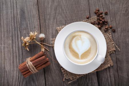 Tasse Cappuccinokaffee auf dem alten Weinleseholztisch, trockene Blume, Zimt, Draufsicht