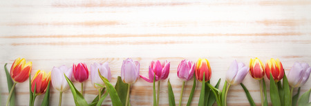 bouquet of tulips of spring flowers on old wooden board on a holiday of Easter Archivio Fotografico