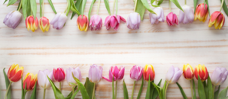 bouquet of tulips of spring flowers on old wooden board on a holiday of Easter
