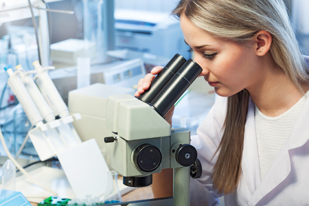 beauty scientist Looks in a microscope in chemical laboratory photo