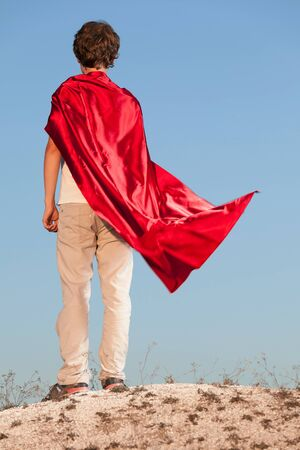 Boy playing superheroes on the sky background, teenage superhero in a red cloak on a hill Stock Photo