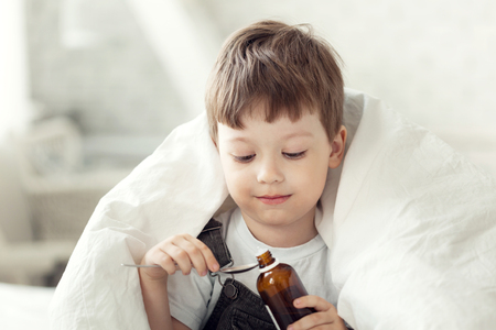 little boy drinking cough syrup Stockfoto
