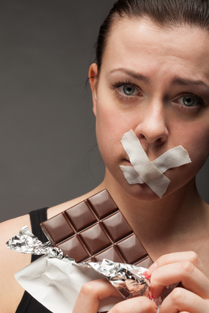 Diet concept: woman holding chocolate with mouth sealed photo