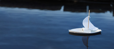 White toy boat at a pier in a pond in summer Stock Photo