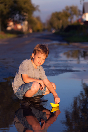 boy play with autumn leaf ship in water, chidren in park play with boat in puddle. Stock Photo