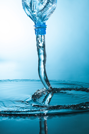 Water flow from a plastic bottle on blue background