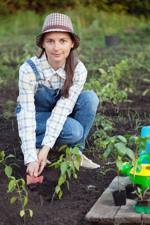 makes: Girl in the garden makes planting seeds Stock Photo