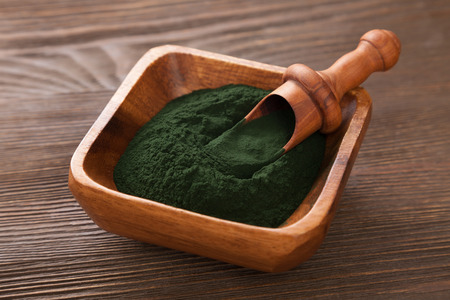 Ground Spirulina on wood background Stock Photo